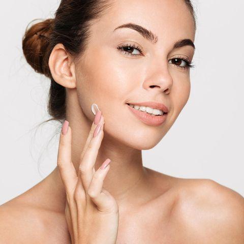 Junge Frau cremt sich das Gesicht ein, Gesichtscreme-Test