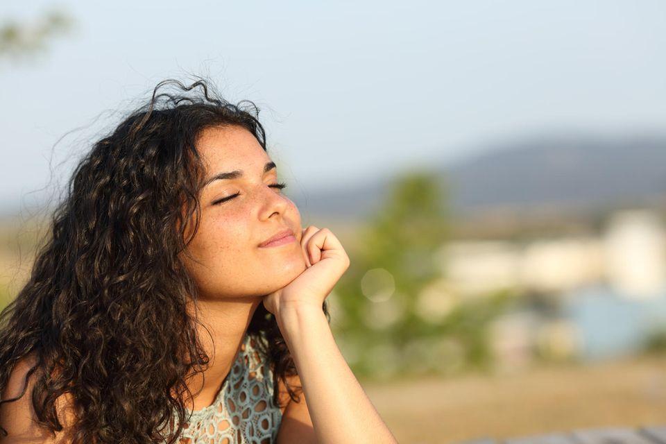 Frau mit Locken entspannt draußen