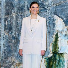 """Wie elegant monochrome Outfits sein können, beweist uns Prinzessin Victoriabeim digitalen Nobelpreisgipfel, der unter dem Motto """"Our Planet, Our Future"""" in Stockholm stattfand. Zur Blazer-Kombination wähltdie schwedische Royal auffällige Creolen aus Gold und eine lange Kette, ebenfalls in Gold."""