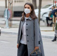 """Königin Letizia zeigt, mit welchen simplen Mitteln ein perfektes Schwarz-Weiß-Outfit gelingen kann. Bei einem Meeting mit der Stiftung """"FundéuRAE"""" in Madrid wertet sie ihren ansonsten recht schlichten Look mit einem karierten Statement-Mantel von Mirto auf. Dazu kombiniert sie eine Bluse von Hugo Boss, eine coole Lederhose von Uterqüe und schwarze Pumps."""