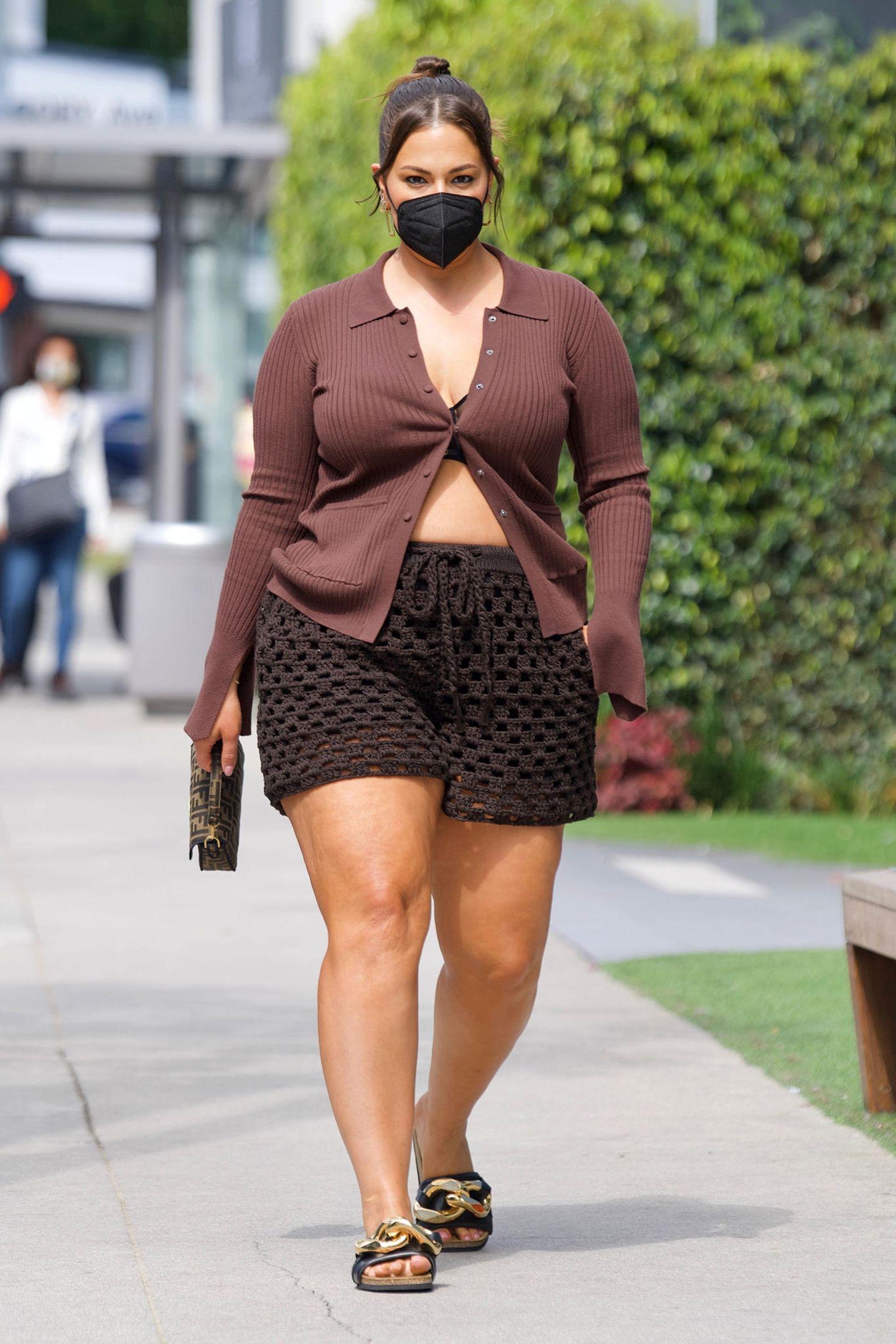 """Strick-Style mit Luxus-Detail: Ashley Graham zeigt sich bei einem Spaziergang durch West Hollywood im rotbraunen Cardigan und breitmaschiger Strick-Short modisch ziemlich entspannt. Aber Luxus muss schließlich sein: ihr kleines Fendi-Täschchen. Und auch ihre """"Chain Loafers"""", Pantoletten mit Kettenglied-Optik in Gold von JW Anderson sind mit 465Euro alles andere als ein Schnäppchen."""