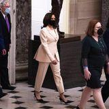 Ihren Anzug in ganz zartem Rosé kombiniert die Vize-Präsidentin mit einem champagnerfarbenen Seidenshirt,und passend dazu trägt sie eine moderne Perlenkette. Pumps und Maske hingegen bilden in Schwarz einen schönen Rahmen.