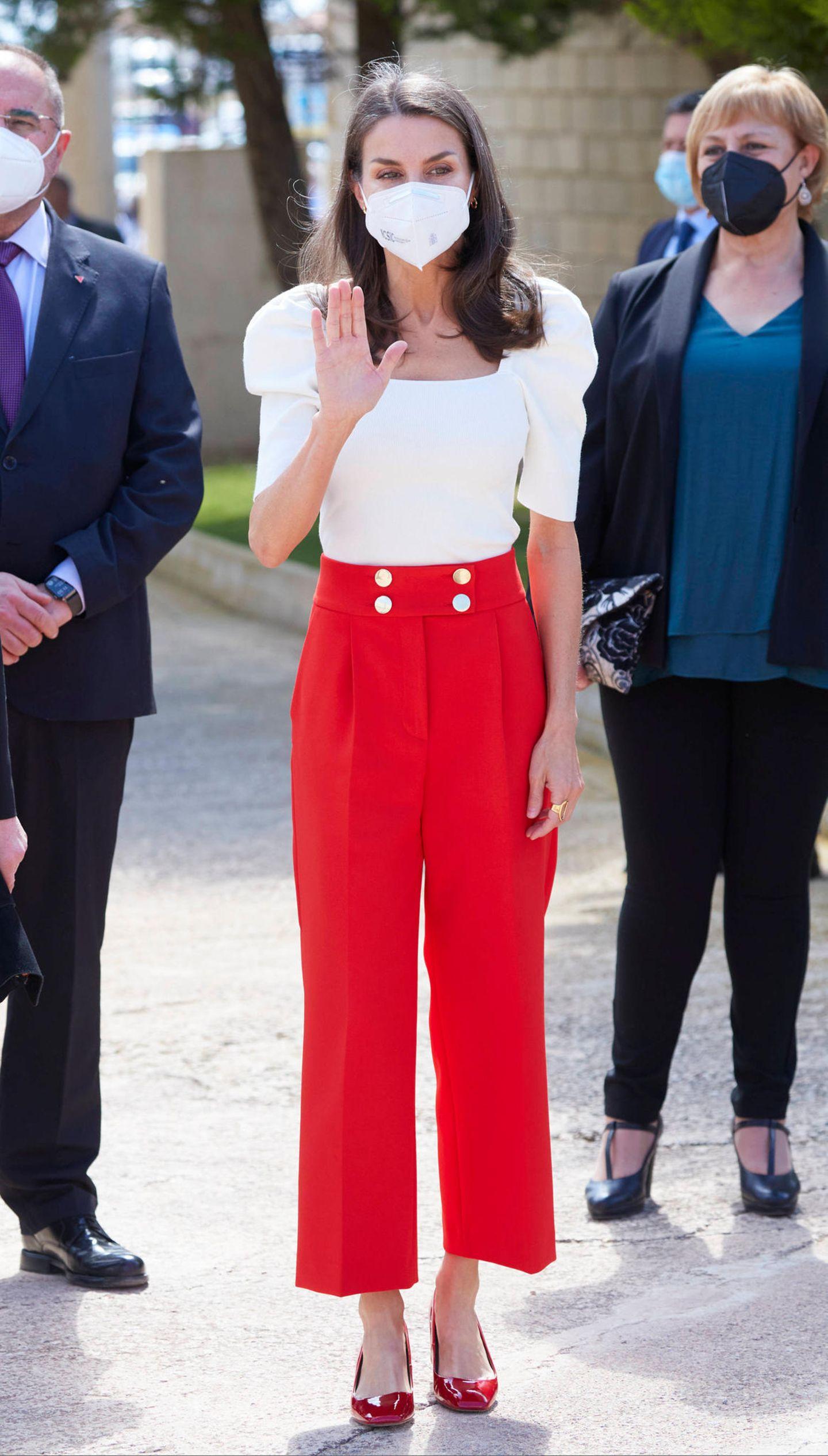 Königin Letizia winkt während des 6. Bildungskongresses für seltene Krankheiten in Totana freundlich den Fotografen zu: doch die haben sie in ihrer auffälligen Outfit-Kombination wahrscheinlich sowieso auf Anhieb wahrgenommen. Die spanische Royal setzt auf eine rote Culotte mit auffälligen Knöpfen am Bund, eine Bluse mit Puff-Ärmeln und auffälligen Lack-Pumps – ebenfalls in Rot. Hierbei handelt es sich um ein Komplett-Outfit des Labels Uterqüe.