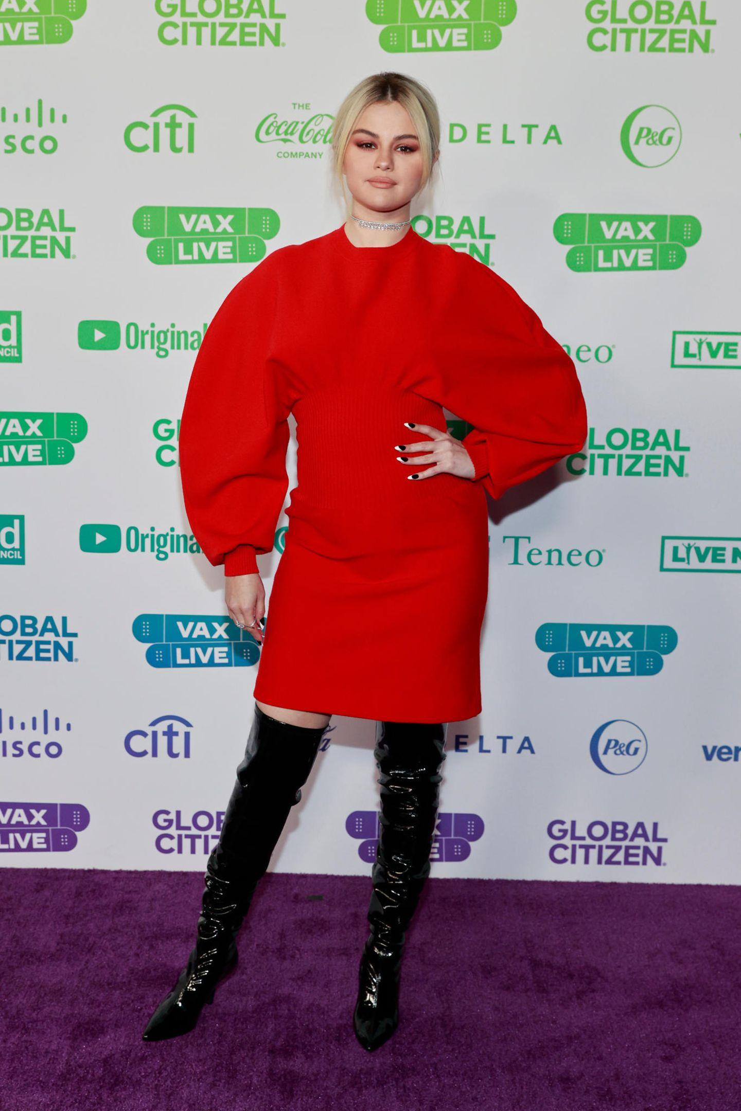 """Es ist das """"Red Carpet""""-Debüt für Selena Gomez' blondeHaare. Die Sängerin ist Moderatorin des Wohltätigkeitskonzerts """"Global Citizen's VAX Live: The Concert to Reunite the World"""" und hat sich aus diesem Grund besonders in Schale geworfen. Zum roten Kleid von Bottega Veneta kombiniert sie einen diamantenbesetzten Choker von Messika."""