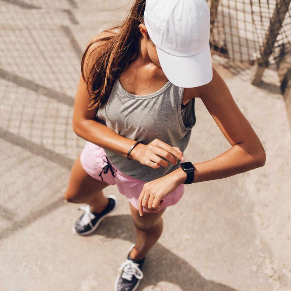 Junge Frau beim Fitness, am Joggen, mit Fitnesstracker, in Sportkleidung