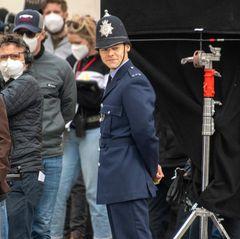 """Da Harry Styles momentan nicht auf den großen Bühnen stehen kann, um für seine Fans zu performen, übt er sich nun als Schauspieler. Die Dreharbeiten für den Film""""My Policeman"""" sind invollemGange und Harry wartet grinsend in der Rolle des Polizisten gekleidet auf seinen Einsatz am Set."""
