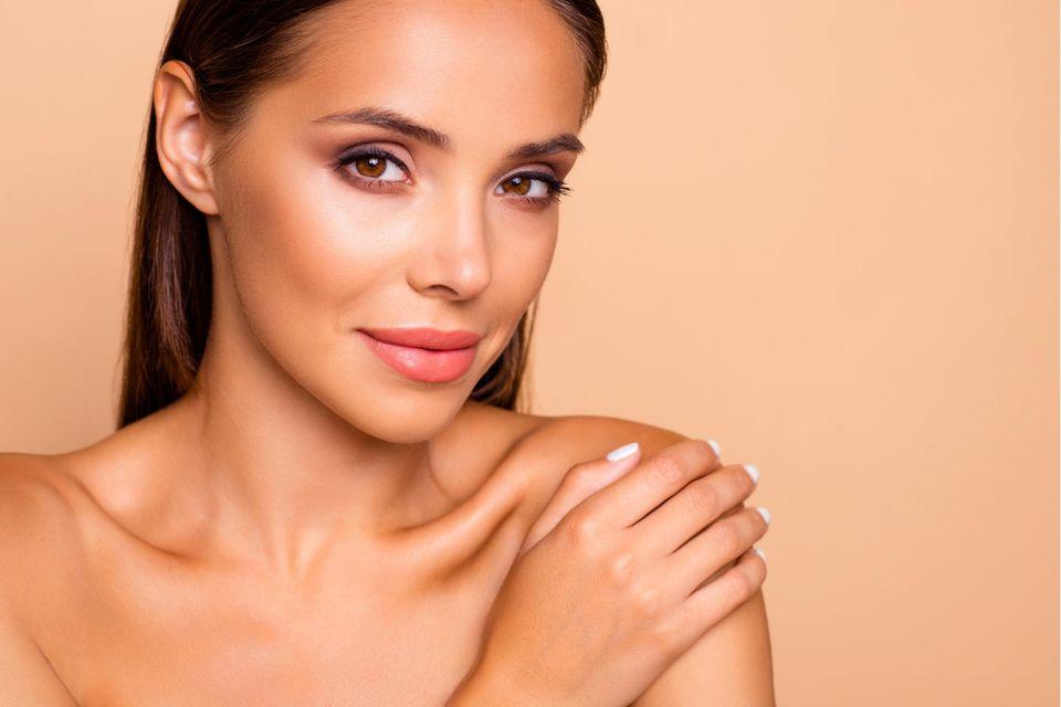 Selbstbräuner-Test: Schöne Haut in wenigen Stunden, Junge Frau mit gebräunter Haut lächelt in die Kamera