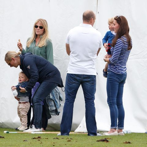 Zara Tindall kümmert sich um TochterLena, während Mike Tindallmit Herzogin Catherine spricht, die Prinz George auf dem Arm hat.