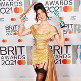 """Sie ist die Abräumerin des Abends. Gleich zwei der Trophäen konnte sich Dua Lipa bei den """"BRIT Awards"""" sichern. Ihr Red Carpet Outfitkann allerdings nicht überzeugen. Die dunklen Strapsen sind einzu harter Stilbruch zum eleganten Kleid im 60's-Look. Da können andere Kolleg:innen eher überzeugen."""