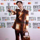"""Harry Styles mausert sich immer mehr zum Fashion-Liebling der Redakteure. Seine Outfits zeugen von Mut, Kreativität und Individualität – so auch bei den """"BRIT Awards"""". Gender-Klischees werden bei ihm über Board geworfen und die """"Gucci Bamboo""""-Tasche stylisch zum 70er-Jahre-Anzug kombiniert."""