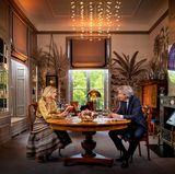 Wow, welch ein imposantes Arbeitszimmer Königin Máxima doch hat!Während eines Interviews anlässlich ihres bevorstehenden fünfzigsten Geburtstages am 17. Mai entstehen diese eindrucksvollen Fotos. Im Homeoffice auf Schloss Huis ten Bosch in Den Haag besucht sie der Journalist Matthijs van Nieuwkerk. Beide sitzen an einem runden dunklen Holztisch mit zwei dazu passenden gepolsterten Stühlen. Auch der Wandschrank,etwas weiter hinten im Raum, scheint aus demselben Holz gefertigt worden zu sein. Auf ihm wirdedles Porzellan gekonnt in Szene gesetzt. Eine Fototapete mit Palmenzeichnungensorgt für karibisches Flair im royalen Arbeitszimmer – extravagante Lichtobjekte tauchen es in ein schönes Licht.