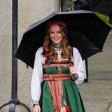 """Prinzessin Ingrid Alexandra trägt eine traditionelle Tracht in den Farben Grün, Rot und Gelb und hält dazu die Landesflagge in der Hand.Die Robe trägt den Namen """"Bunad"""" und ist ein Geschenk von ihren Großeltern Königin Sonja und König Harald. Das traditionelle Kleidungsstück stammt aus Aust-Telemark und erinnert an die Trachten, die schon um das Jahr 1810 von den norwegischen Frauen getragen wurden."""