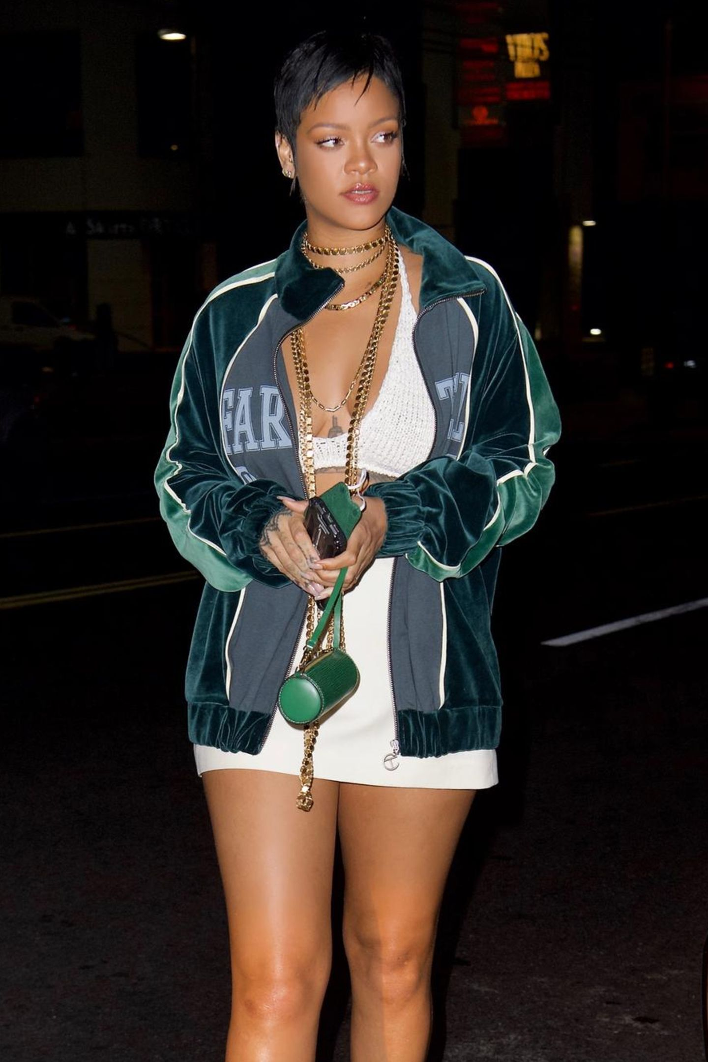 """Huch, wurde die Zeit hier etwa zurückgedreht? Irgendwie kommt uns Rihannas Look doch bekannt vor... Genau, diesePixie-Frisur erinnert an die Anfänge ihrer Karriere,als sie Hits wie """"Rude Boy"""" oder """"Russian Rouletteveröffentlichte. Bei einem Abendessen mit Freunden trägt sie ein tief ausgeschnittenes Top und einen dazu passenden Rock. Damit das Outfit etwas cooler wirkt, kombiniert sie dazu eineTrainingsjacke und Goldketten."""
