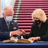 Prinz Charles und Herzogin Camilla tragen sich bei ihrem Termin in Belfast in das Buch der Stadt ein.