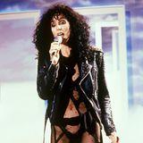 """""""If I Could Tuuuuurn Back Time"""" – wer dieses Foto sieht, bekommt direkt einen Ohrwurm! ChersHit von 1989 ist genauso ikonisch, wie ihr Look: schwarze Lockenmähne und ein Outfit, das wirklich nur das Nötigste verdeckt. Über 30 Jahre später ist Cher ihrem Signatur-Stil definitiv treu geblieben. Staunen Sie selbst …"""