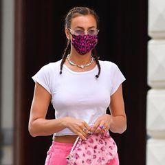 Irina Shayk gehört zu den stylischsten Topmodels der Welt. Und auch bei diesem Outfit wird schnell klar: an Irina geht kein Trend vorbei. Mit ihren Trackpants von Cotton Ciziten in Neonpink schlendert sie in einer der angesagtesten Farben des Sommers durch NYC. Dazu trägt sie lässige Adidas-Sneaker, ein T-Shirt von Eterne und kleine Creolen von Jennifer Zeuner.