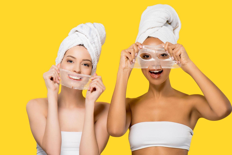 Fröhliche Frauen mit Gesichtsmasken, pflegende Hydrogel-Masken für Hautpflege