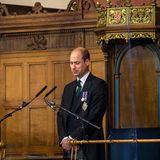 """Mit einer Rede und einem Lächeln eröffnet der Prinz die Generalversammlung der """"Church of Scotland"""". Aber auch in der Assembly Hall sind coronabedingte Sicherheitsvorkehrungen getroffen worden:William steht hinter eine großen Glasscheibe."""