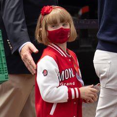 """Prinzessin Gabriella zeigtbeim Großen Preis von Monaco im Rahmen der Formel 1 in Monte-Carlo schon, dass sie eine echte Lokalpatriotin ist: In süßer College-Jacke mir großem""""Monaco""""-Schriftzug flitzt sie hinter den Kulissen umher. Maske und Haarreif passen farblich perfekt."""