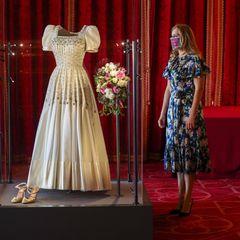 """23. September 2020  Prinzessin Beatrice und Edoardo Mapelli Mozzi mussten wegen der Corona-Pandemie auf ihre große Hochzeit verzichten. Stattdessen traute sich das royale Paar am 17. Juli heimlich in einer Minizeremoniein der """"Royal Chapel of All Saints"""" in Windsor. Das Hochzeitskleid von Prinzessin Beatrice sorgte dabei jedoch für einen riesigen Wow-Effekt. Das wunderschöne Kleid mit dem diamantenbesetztem Miederist eine Vintage-Kreation, die eigens für Queen Elizabeth entworfen und 1962 auch von ihr bei einer Filmpremiere getragen wurde.  Zwei Monate nach ihrer Trauung besucht Prinzessin Beatrice ihrHochzeitskleid, das in einer Ausstellung auf Schloss Windsor auch für die Öffentlichkeit zu bewundern ist."""