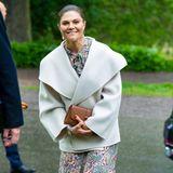 Prinzessin Victoria strahlt bei der Jahresversammlung des Museums Skansen gegen den Regen an. Sie trägt ein geblümten Kleid der Marke TiMo, einen Mantel von Toteme, braune Pumps von Gianvito Rossi und Perlenohrringe der Marke Cravingfor