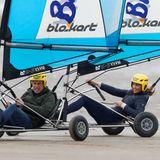 In den windbetriebenen Strandfahrzeugen liefert sich das ehrgeizige Paar ein rasantesWettrennen, das für sichtlich Spaß sorgt.
