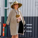 Máxima, bist du es? Ihrem extravaganten Outfit nach zu urteilen, könnte die niederländische Königin auch mit einer Stil-Ikone der 50er-Jahre verwechselt werden. Zum XXL-Hut kombiniert sie ein Etuikleid, über das sie lässig einen Mantel geworfen hat – beides stammt von MáximasLieblingslabel:Natan Couture. Die Pumps sind von Gianvito Rossi und passen farblich zur Clutch.