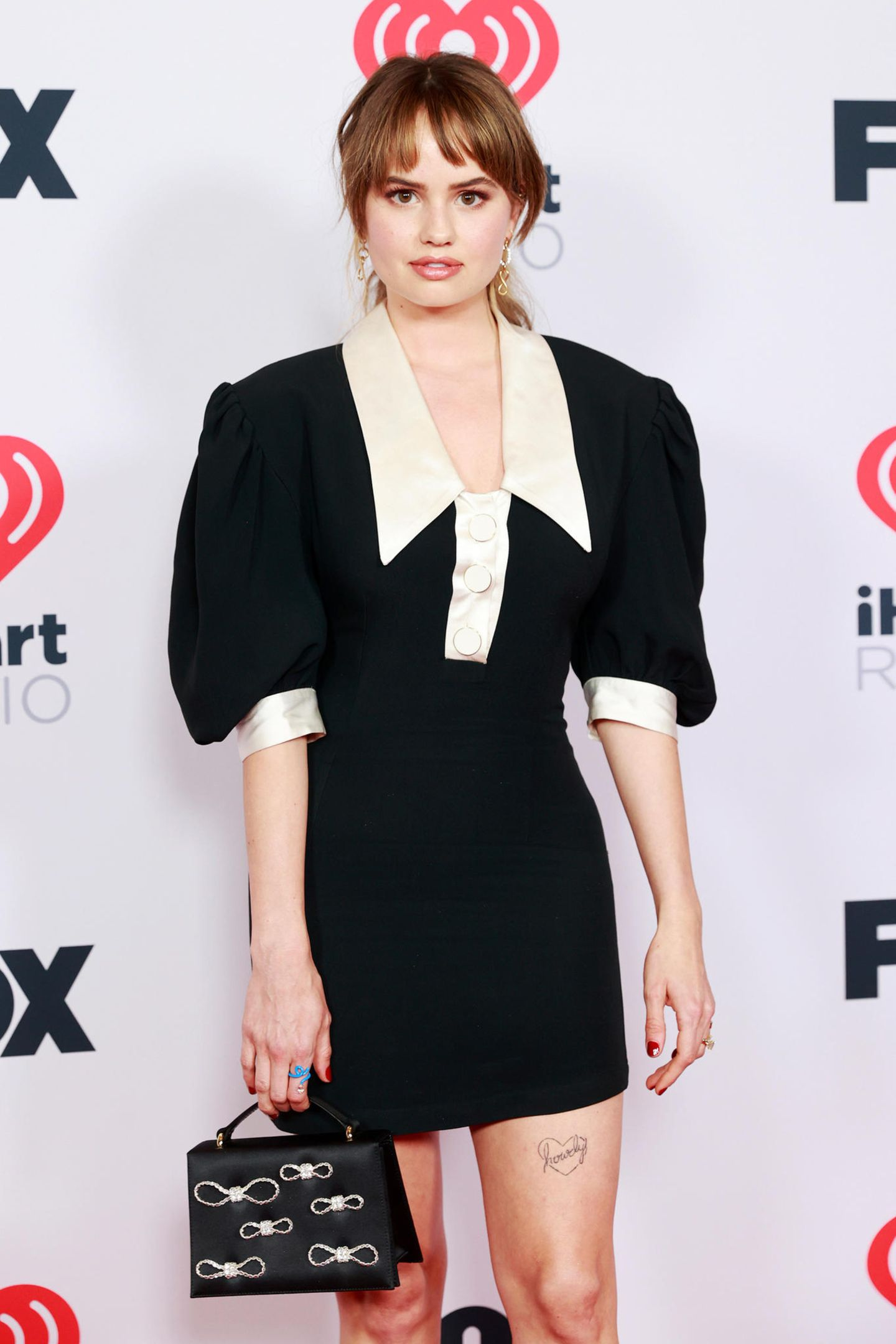 """Fast brav im schwarz-weißen Dress mit Puffärmeln läuft """"Insatiable""""-Star DebbyRyan über den roten Teppich der iHeartRadio Music Awards."""