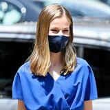 """Zum Blau des Kleides passend trägt sie eine dunkelblaue Maske mit dem Wappen ihrer Schule Santa María de los Rosalesund darunter das Motto """"Sin Pérdida de Su Luz"""",was übersetzt soviel wie """"Ohne dein Licht zu verlieren"""" bedeutet."""