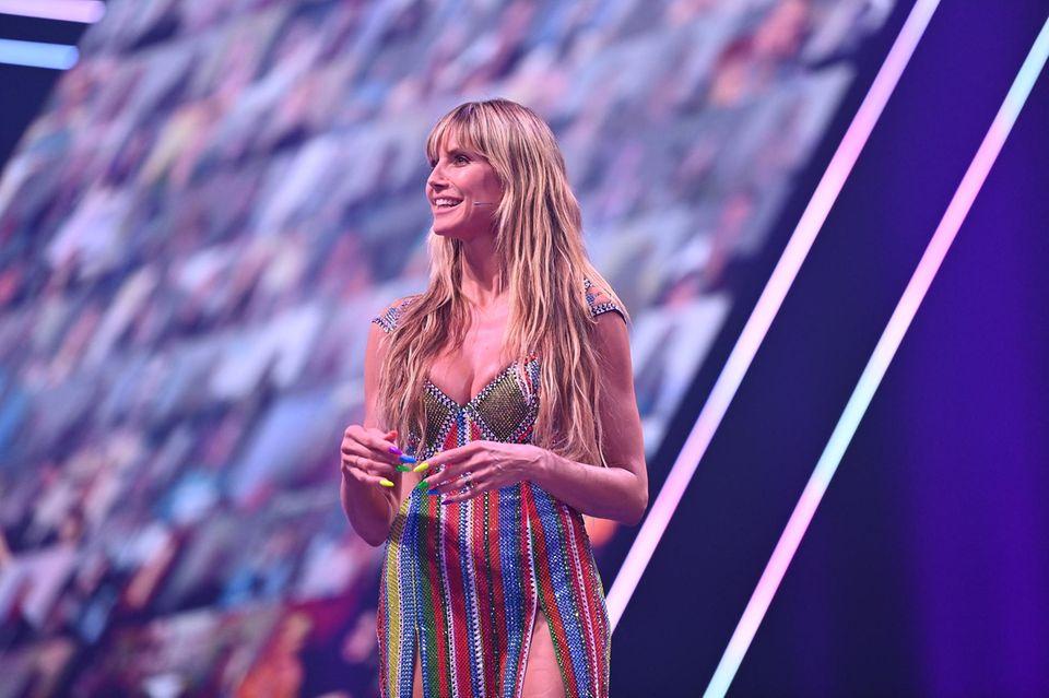 Was für ein Bling-Bling-Dress! In ihrem bunten Kleid von Versace stiehlt Heidi Klum beimGNTM_Finale 2021 ihren Kandidatinnen beinahe die Show. Allerdings fallen die Blicke nicht nur auf ihr Outfit, sondern auch auf die Fingernägel. Die langen Ballerina-Nails in grellen Regenbogenfarben scheinen dann doch eine Spur zu viel zu sein. Aber genauso kennt man das Topmodel – ihr Geschmack ist eben besonders und ausgefallen ...