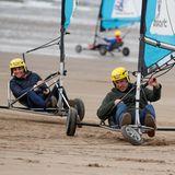 Am Strand der schottischen Kleinstadt St. Andrews dürfen sich Herzogin Catherine und Prinz William im Strandsegelnausprobieren. In den windbetriebenen Fahrzeugen liefert sich das ehrgeizige Paar ein rasantesWettrennen, das für sichtlich Spaß sorgt.