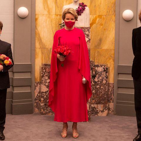 Pink gewinnt: Bei der Verleihung des Piano-Wettbewerbs trägt Königin Mathilde ihrbekanntes pinkfarbenes Cape-Kleid der Marke Natan, Mund-Nasenschutz und Blumen sind perfekt darauf abgestimmt, die goldenen Heels setzen einen glänzenden Kontrast.