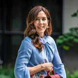 Diesen sommerlichen Look kombiniertdie dänische Kronprinzessin wie üblich gekonnt mit passenden Accessoires: Die rote Nathalie-Handtasche stammt von Boss, und an ihren Ohren und am Ringfinger trägt Mary farblich zur Bluse passende Schmuckstücke.