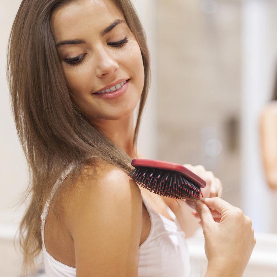 Haarbürste reinigen: Frau mit Haarbürste