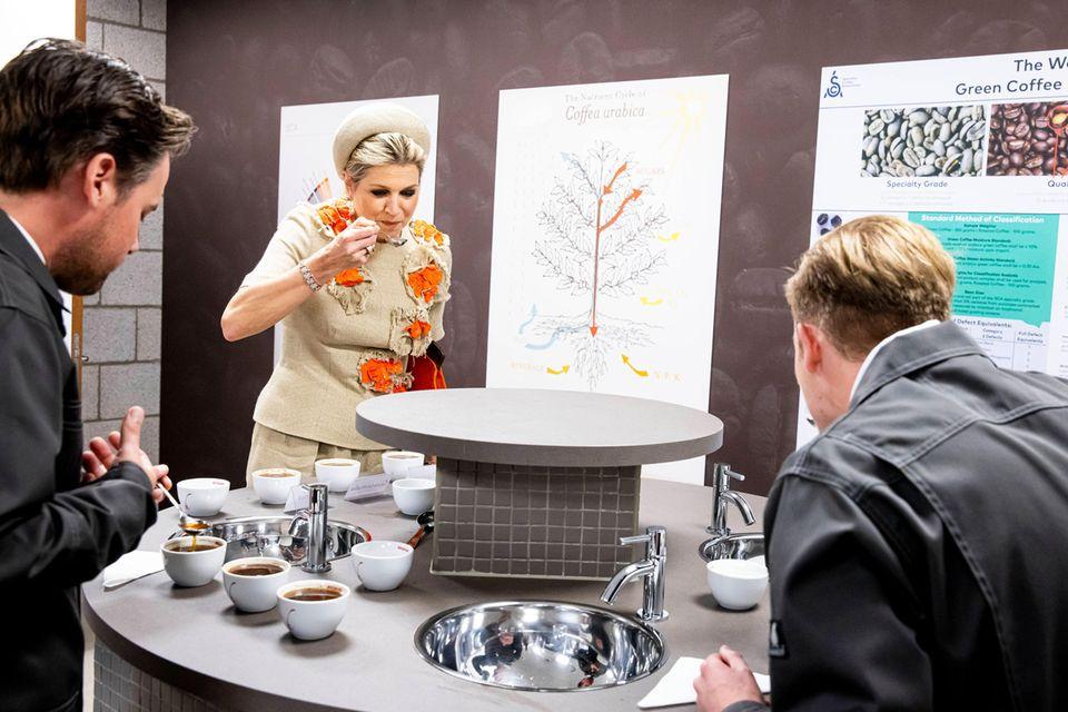 """Königin Máxima gönnt sich einen kleinen Koffeinkick am Nachmittag. Fröhlich besucht sie die Eröffnung des neuen Gebäudes der Kaffeerösterei """"Hesselink Koffie"""" und verkostet sogleich ein paar edle Sorten. Ein royales Kaffeekränzchen ganz nach dem Geschmack der Königin der Niederlande."""