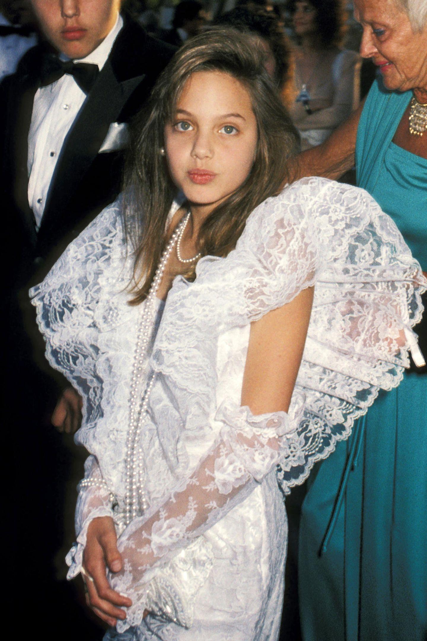 1986  Als Tochter desSchauspielerpaars Jon Voight und Marcheline Bertrand wächst Angelina Jolie mit dem Glamour und Trubel Hollywoods auf. Als niedliche Zehnjährige gab sie sogar schon ihr Debüt auf dem roten Teppich der Oscars, ganz unschuldig im weißen Spitzenkleid.