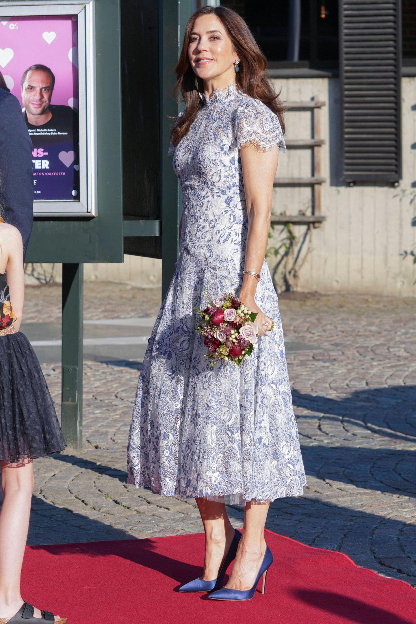 """Weiße Spitze sieht nicht nur bei Brautkleidern umwerfend aus, mit kleinen Farbakzenten wird der edle Stoff zum sommerlichen Eye-Catcher, das beweist Prinzessin Mary bei den Feierlichkeiten zur Konzertreihe """"Mind the Music"""" in Odense. Mit dem Spitzentraum unterstützt MaryDesigner:innen (Moss & Spy) aus ihrer Heimat Australien."""