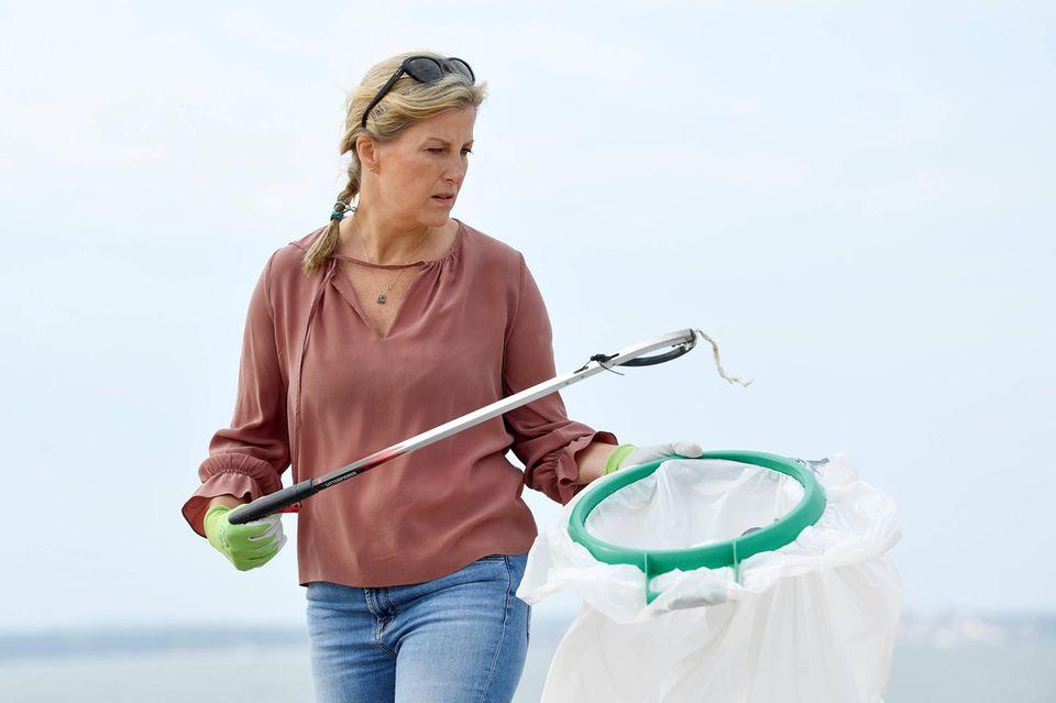 Während des Müllsammelns am Strand bleibt der große Müllbeutel nicht lange leer. Für den Umweltschutz packt Gräfin Sophie von Wessex fleißig mit an.