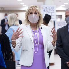 Zum Flieder-Look trägt Jill klassischen Perlenschmuck, und auch ihre Mundschutz passt farblich perfekt, die Seidenmaske ist seitlich mit zarten violetten Blütenmotiven bestickt.