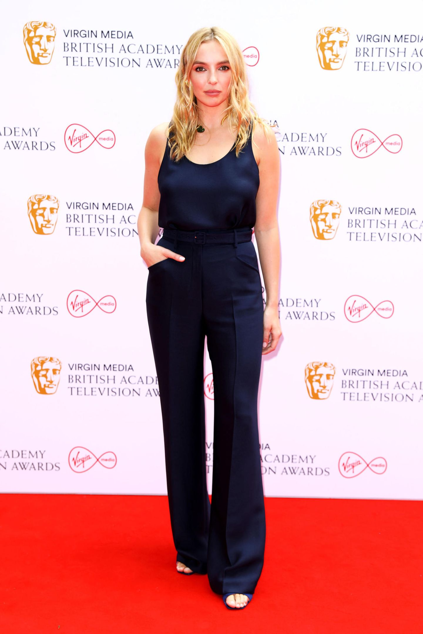 """Lässig in Dunkelblau: Mit eleganter Anzughose zum passenden Seidentop zeigt sich """"Killing Eve""""-Star Jodie Comer bei der diesjährigen Verleihung der BAFTAs zwar eherunglamourös, aber sommerlich elegant."""