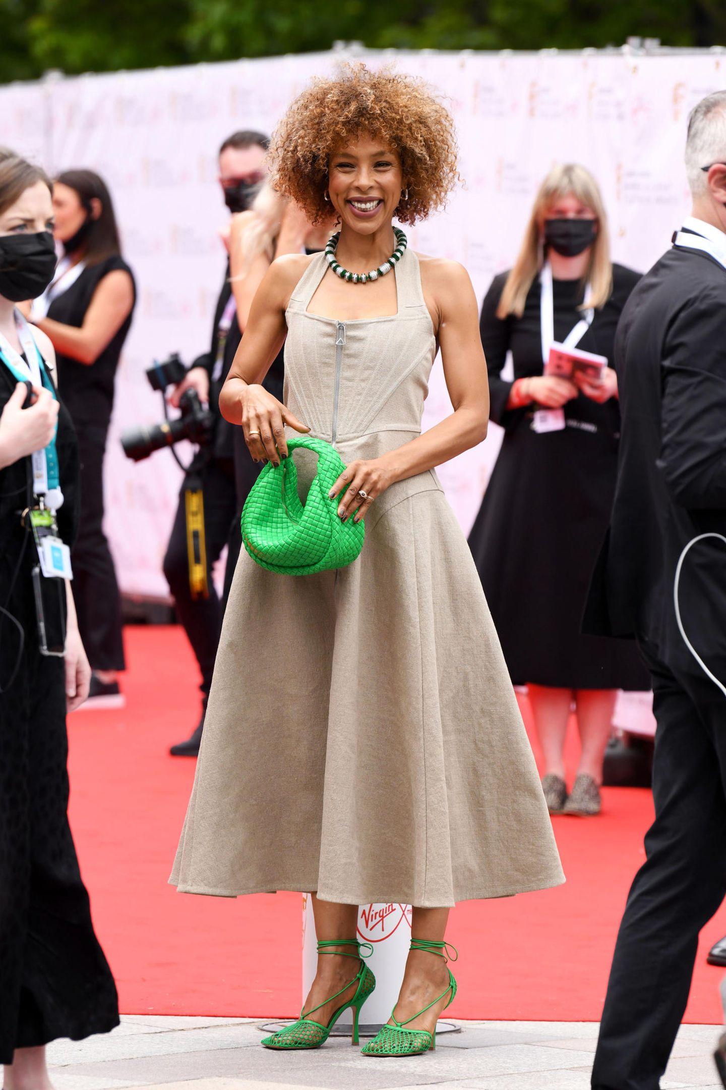 Sophie Okonedo setzt mit ihrer leuchtend grünen Handtasche undpassenden Heels tolle farbliche Akzente zum dezenten, beigefarbenen Leinen-Dress.