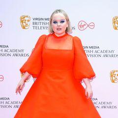 """""""Bridgerton""""-StarNicola Coughlan ist in ihrem Valentino-Kleid der farbliche Hingucker des Abends, und die pinkfarbenen High Heels und der leuchtend blaue Lidschatten sind tolle Kontraste zum kräftigen Orange."""