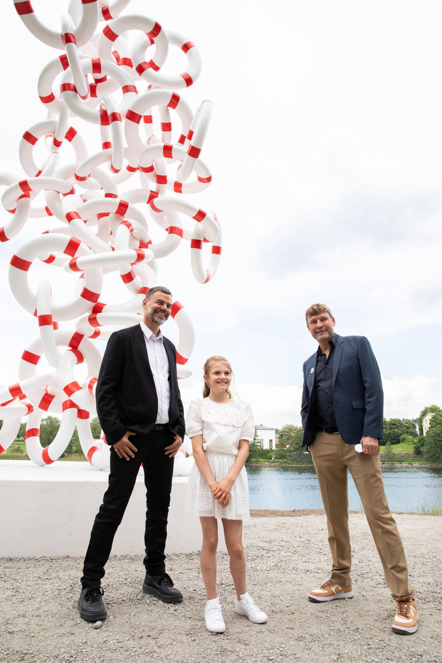 Kleine Kronprinzessin ganz groß: Prinzessin Estelle weiht im StockholmerDjurgården eine Skulptur ein und posiert dafür mit den Künstlern für die Fotografen. Sie trägt eine niedliche Kombibestehend aus weißer Bluse mit Spitzenkragen und einem weißen Röckchen. Auf der Bluse von Bonpoint (rund 210 Euro) sind kleine rosa Blumen zu erkennen. Dazu kombiniert sie weiße Stan-Smith-Sneaker.