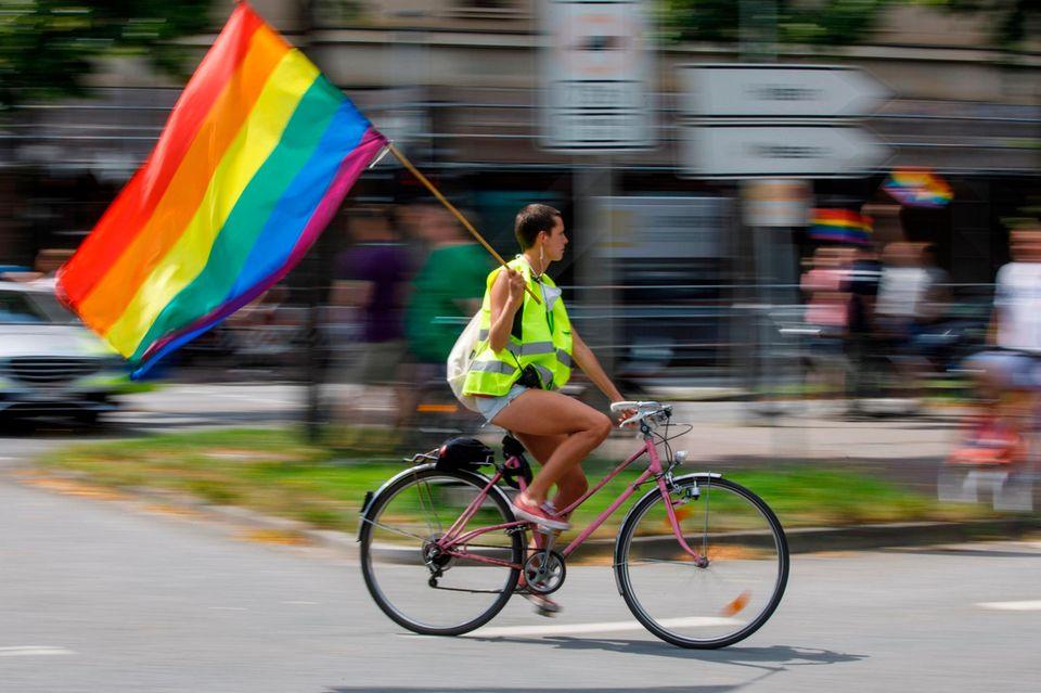 Pride Week: Deswegen ist sie uns so wichtig, Regenbogenfahne, Fahrradfahrerin