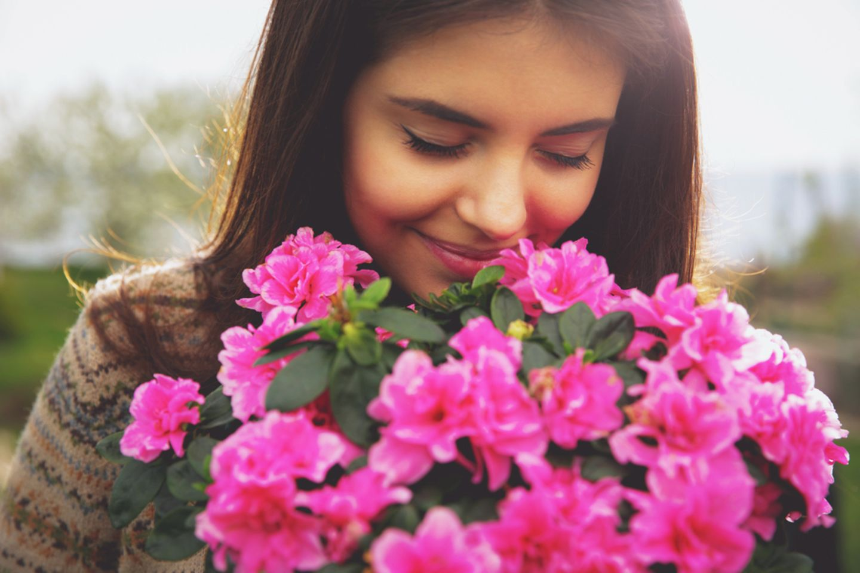 Geburtsblume: Frau riecht an Blumen.