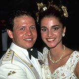 Zu den Feierlichkeiten am Abend wechselt das royale Brautpaar ihre Looks noch einmal: Prinz Abdullah trägt nun eine weiße Uniform, Rania tauscht ihren Schleier gegen floralen Schmuck im Haar und einen leichteren Bustier-Look mit den gleichen blumigen Applikationen.