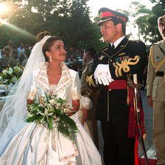 10. Juni 1993  Traumhochzeit im Königreich Jordanien:Prinz Abdullah heiratet seine Angebetete Rania Yasin im Königlichen Palast in Amman, und die zukünftige Königin strahlt dabei in einem schimmernden Satinkleid mit Jäckchen mit großem Kragen und aufwendigen, gold-floralen Stickereien.