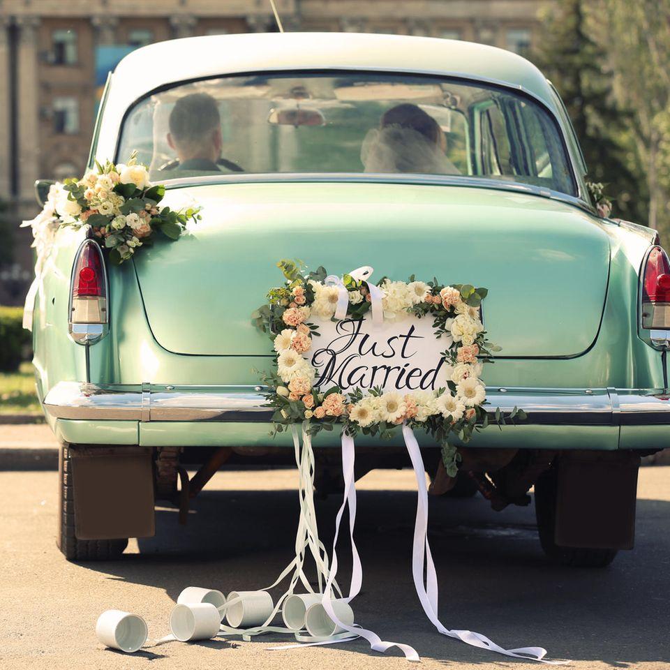 Autoschmuck Hochzeit: So dekorieren Sie das Brautauto, Brautpaar sitzt in geschmücktem Hochzeitsauto