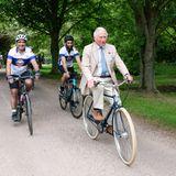 """Währenddessen radelt Prinz Charles beim Start des Charity-Radsport-Events """"Palaces on Wheels"""" vorne weg und freut sich über die vielen Teilnehmer inGloucestershire."""