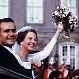 Ihr edler Spitzenschleier, der mit einem schwungvollen Diamantdiadem kombiniert wurde, trug die Margrethes spätere Schwiegertochter Prinzessin Mary übrigensauch bei ihrer Hochzeit.  Das Brautbouquet der zukünftigen Königin war ein sommerliches Gesteck mit Margeriten, weißen Rosen und Cyrtanthus-ähnlichen weißen Blüten. Und noch ein traurig-schönes Details: Als Prinzgemahl Henrik im Jahr 2018 verstarb, trug Margrethe die schönen Perlenohrringe ihrer Hochzeit als letzten Gruß auch bei seiner Beerdigung.